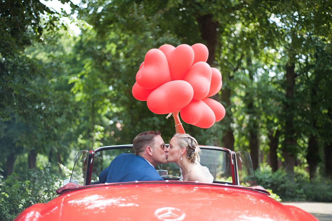 Rudek Fotografie - Hochzeitspaar im Cabrio mit Luftballons