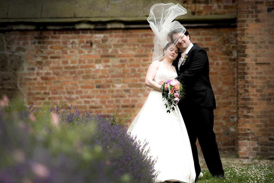 Rudek Fotografie Hochzeitspaar vor einer Ziegelwand